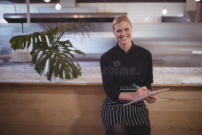 Porträt der jungen attraktiven Kellnerin, die mit Klemmbrett sitzt lizenzfreie stockfotografie