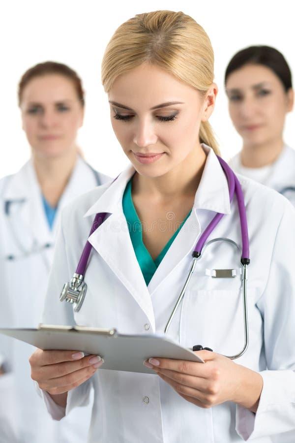Porträt der jungen blonden Ärztin umgeben durch medizinischen Tee stockbild