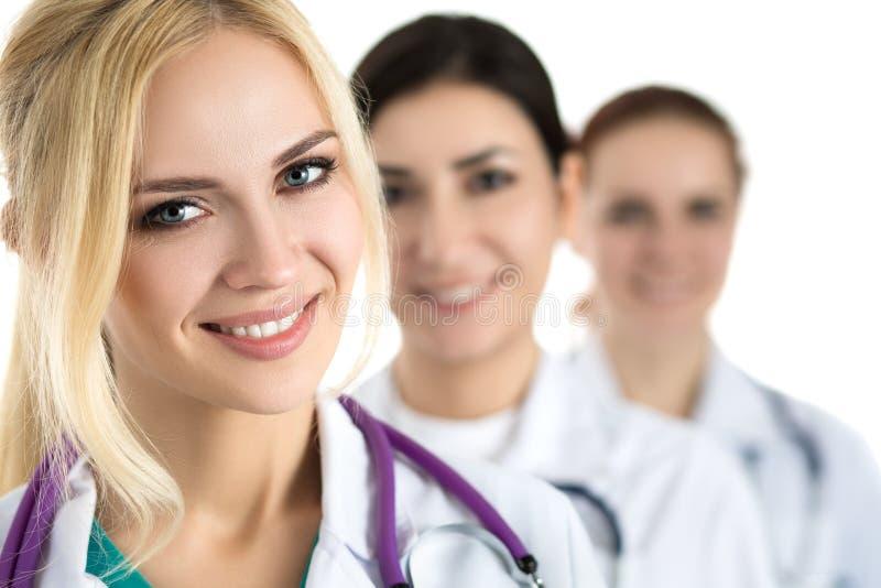 Porträt der jungen blonden Ärztin umgeben durch medizinischen Tee lizenzfreies stockbild