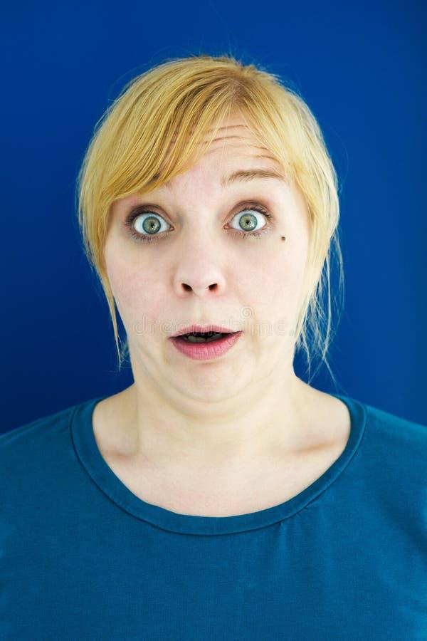 Porträt der jungen blonden Frau, die überrascht schaut stockfotos