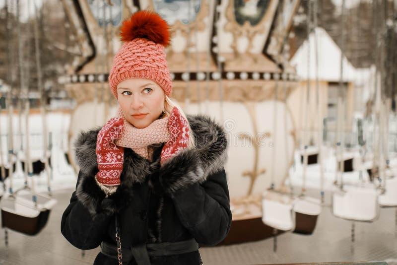 Porträt der jungen blonden Frau in der Winterkleidung Rote Kappe und Handschuhe Gehen in den Park lizenzfreie stockfotos