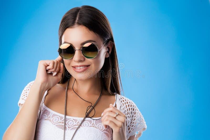 Porträt der jungen brunette Frau, die ihr Ohr durch Finger, hörende Musik in den Kopfhörern versteckt Tragende weiße Spitze, Knit stockbild