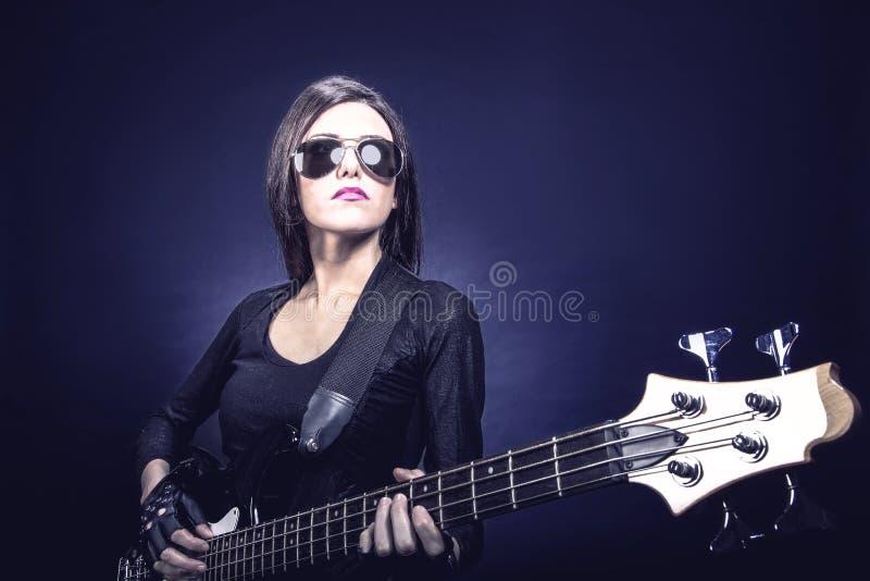 Porträt der jungen Brunettefrau, die Baß spielt lizenzfreies stockbild