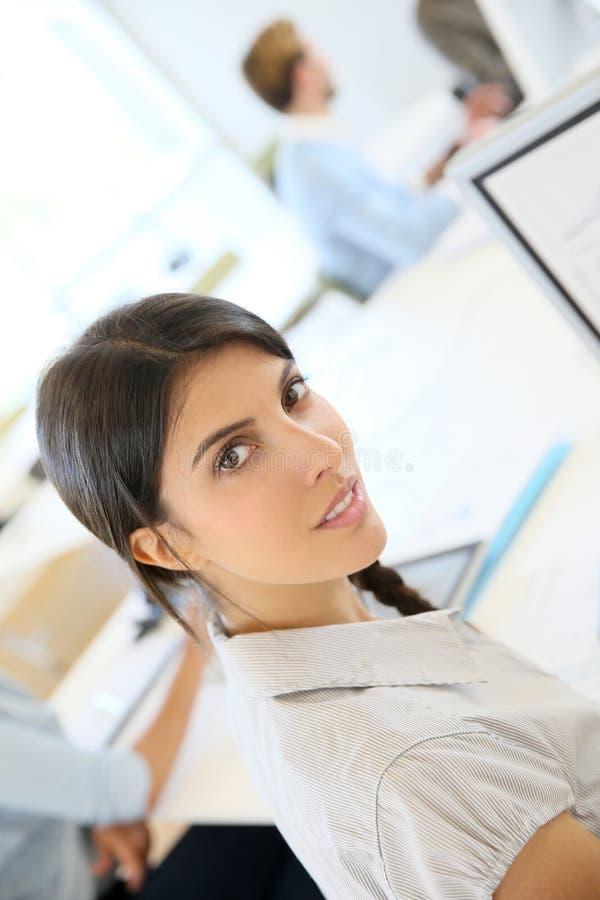 Porträt der jungen Brunettefrau, die an Computer arbeitet lizenzfreie stockfotos