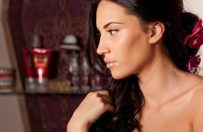 Porträt der jungen Brunettefrau mit dem gelockten Haar im Raum stockfotografie