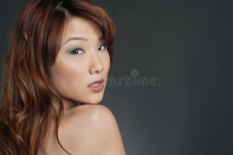 Porträt der jungen Chinesin mit dem Lidschatten, der zurück über farbigem Hintergrund schaut lizenzfreie stockfotografie