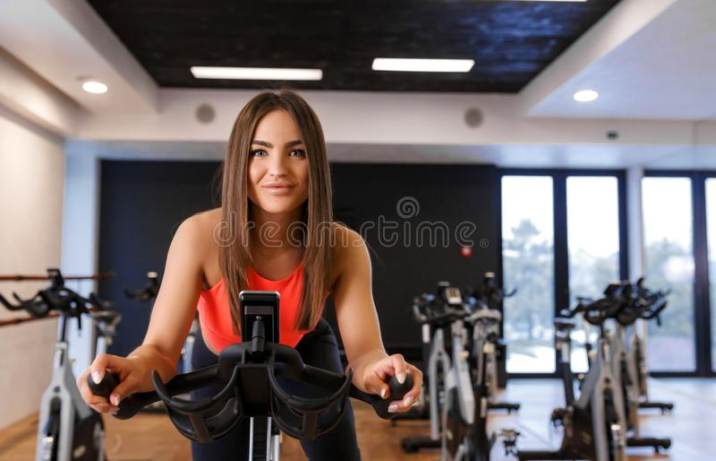 Portr?t der jungen d?nnen Frau in sportwear Training auf Hometrainer in der Turnhalle Sport- und Wellnesslebensstilkonzept lizenzfreies stockbild