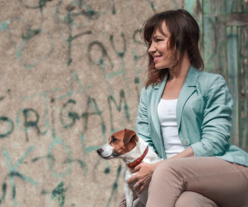 Porträt der jungen erwachsenen kaukasischen hübschen Frau, die kleinen Hundesteckfassungsrussel-Terrier am Sommertag sitzt und um lizenzfreies stockbild