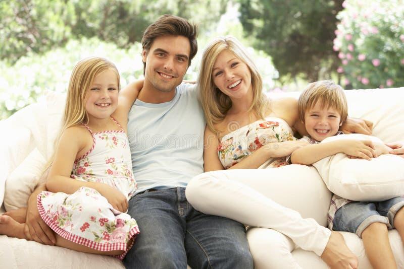 Porträt der jungen Familie entspannend auf Sofa stockfotos