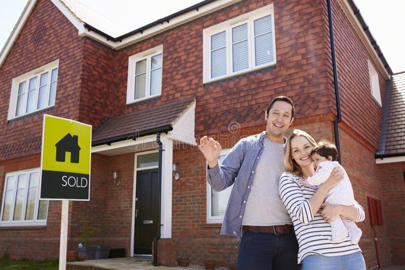 Porträt der jungen Familie mit Schlüsseln zum neuen Haus stockbilder