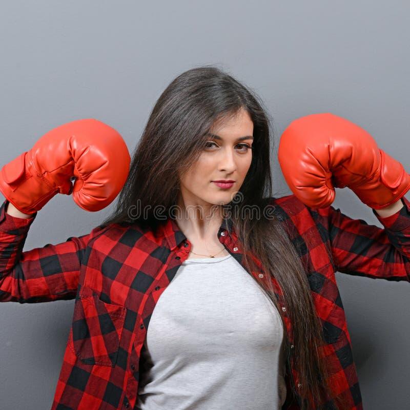 Porträt der jungen Frau aufwerfend mit Boxhandschuhen gegen grauen Hintergrund stockbild