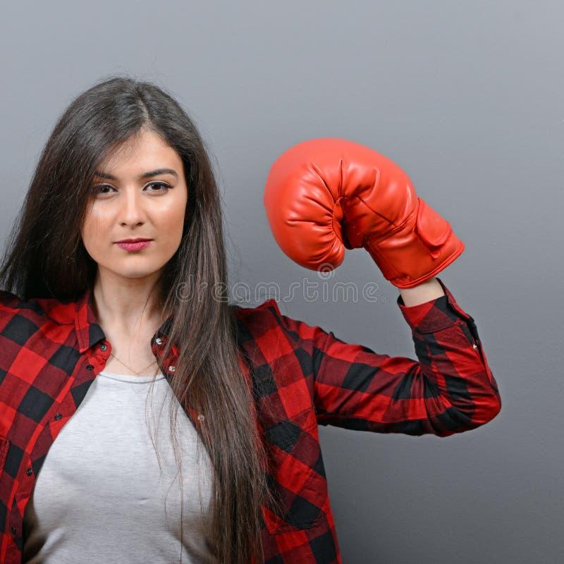 Porträt der jungen Frau aufwerfend mit Boxhandschuhen gegen grauen Hintergrund lizenzfreie stockfotos