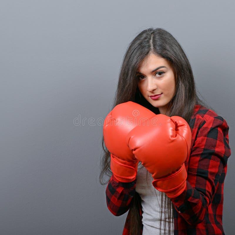 Porträt der jungen Frau aufwerfend mit Boxhandschuhen gegen grauen Hintergrund lizenzfreies stockbild