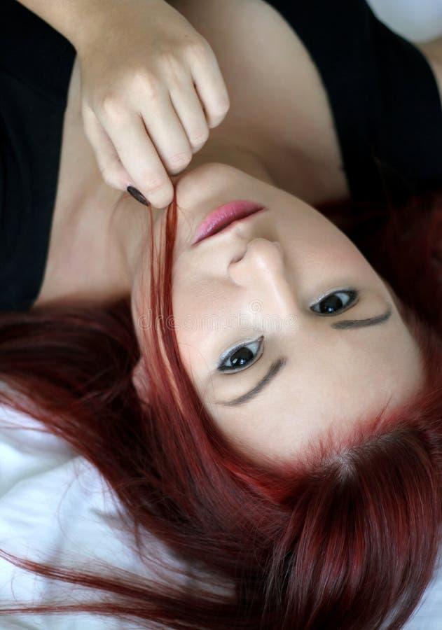 Porträt der jungen Frau der Rothaarigen, das auf das Bett legt lizenzfreie stockfotografie