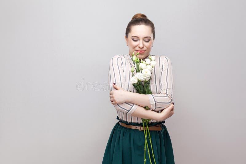 Porträt der jungen Frau des attraktiven romantischen Vergnügens in gestreiftem Hemd und grüner Rockholdingblumenstrauß von weißen lizenzfreie stockfotografie