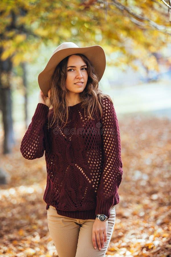 Porträt der jungen Frau des glücklichen Lächelns, die draußen in Herbstpark in der gemütlichen Strickjacke und im Hut geht Warmes lizenzfreies stockbild