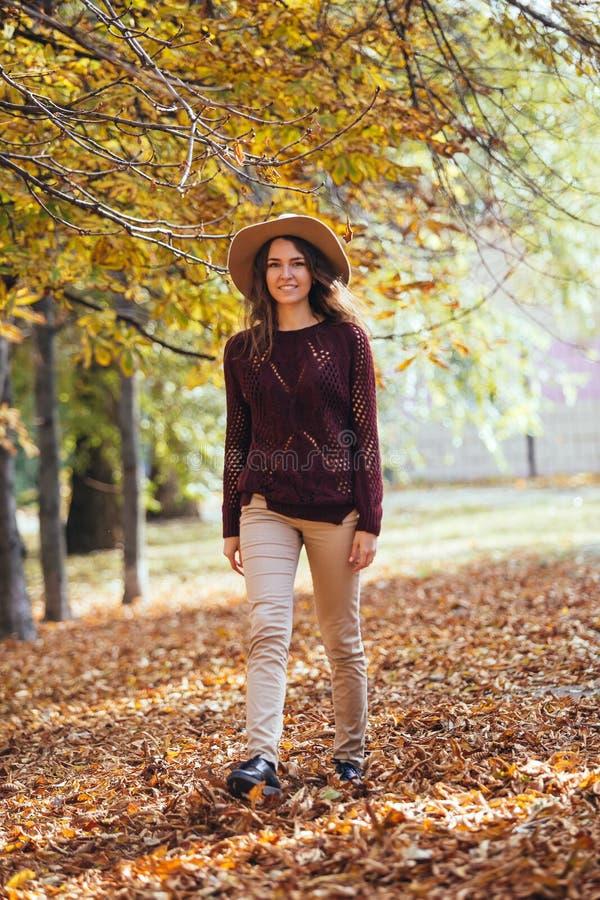 Porträt der jungen Frau des glücklichen Lächelns, die draußen in Herbstpark im gemütlichen Mantel und im Hut geht Warmes sonniges lizenzfreie stockfotos