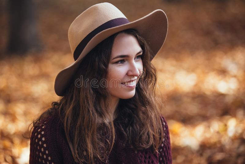 Porträt der jungen Frau des glücklichen Lächelns draußen im Herbstpark in der gemütlichen Strickjacke und im Hut Warmes sonniges  stockfoto