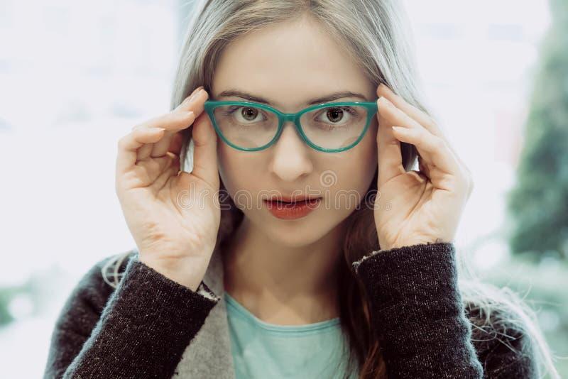 Porträt der jungen Frau die Gläser an versuchend stockbilder