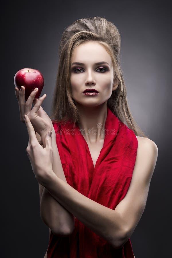 Porträt der jungen Frau in einem roten Schal mit einer Avantgardefrisur, die in der Hand roten Apfel auf einem grauen Hintergrund stockfoto