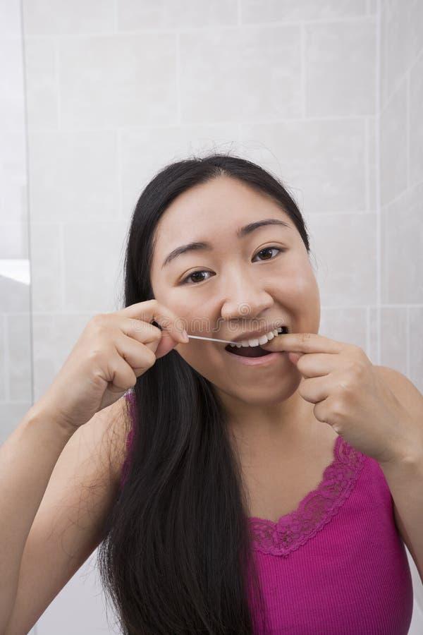 Porträt der jungen Frau flossing ihre Zähne im Badezimmer stockfotografie