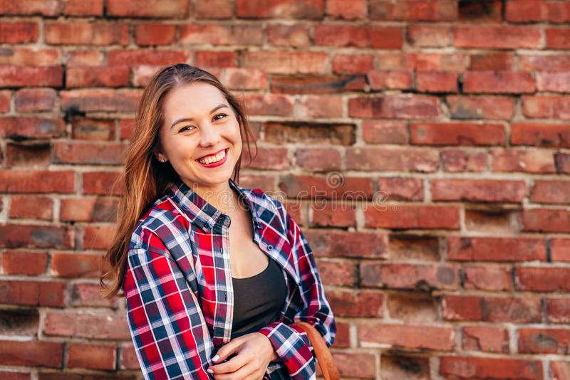 Porträt der jungen Frau gegen Backsteinmauer lizenzfreie stockfotografie