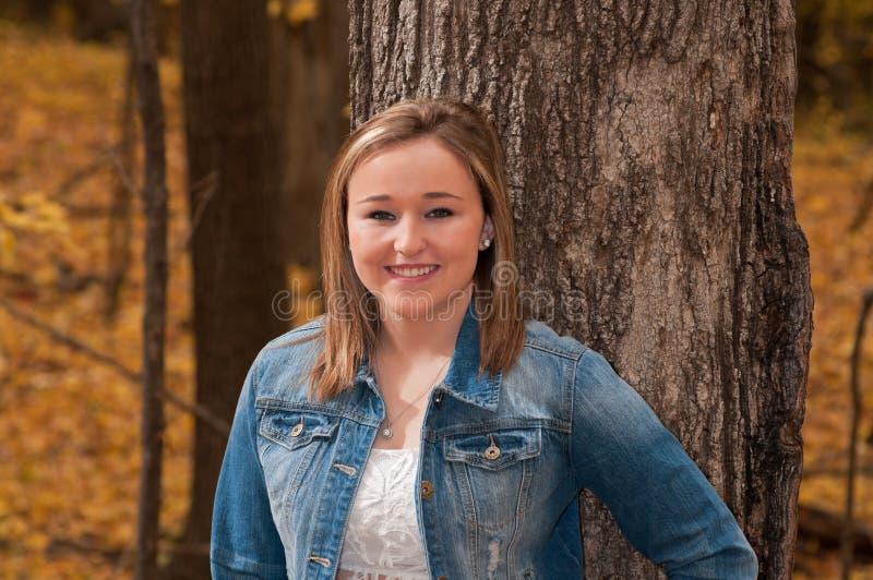 Porträt der jungen Frau gegen Baum stockbild