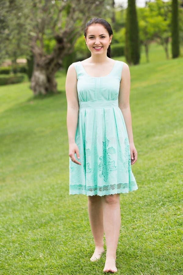 Porträt der jungen Frau im Kleid nahe Rosen in einem Freien lizenzfreie stockfotografie