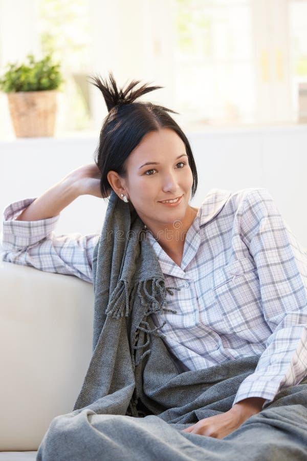 Porträt der jungen Frau im Pyjama, der Decke hat