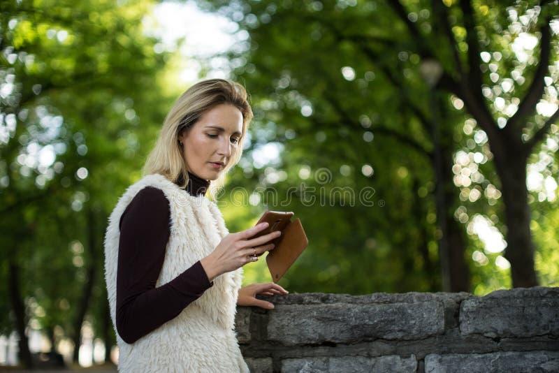 Porträt der jungen Frau im Sommer Blondes Mädchen liest Mitteilung am Handy draußen in der Stadtnatur Frau mit Telefon lizenzfreie stockfotografie