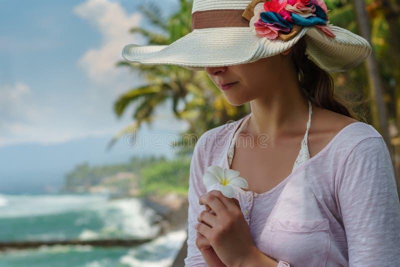 Portr?t der jungen Frau im Sommerhut mit gro?en bunten Blumen ist l?chelnd halten und wei?e tropische Blume auf dem Ozeanstrand lizenzfreie stockfotos