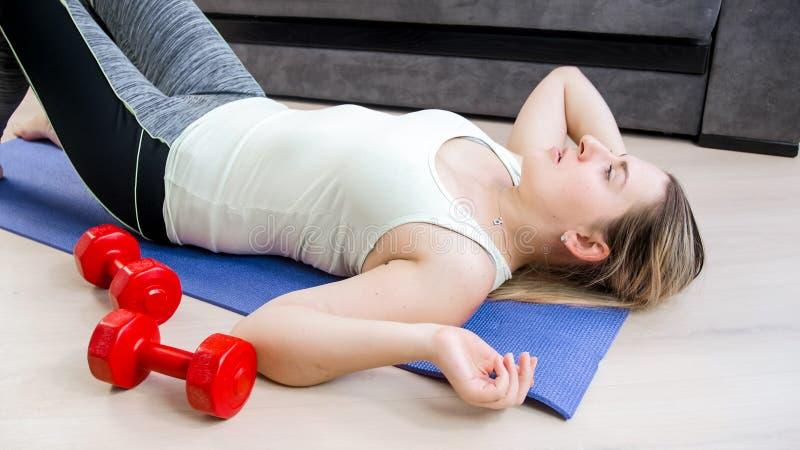 Porträt der jungen Frau kaum atmend nachdem dem Trainieren auf Boden am Wohnzimmer lizenzfreies stockbild