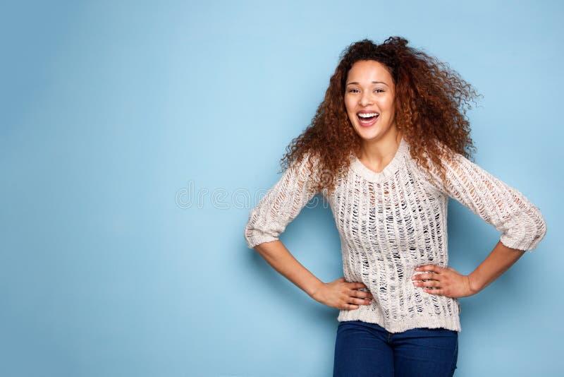 Porträt der jungen Frau lächelnd gegen blaue Wand stockbilder