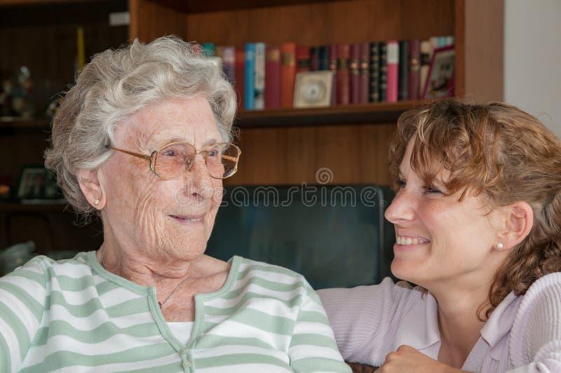 Porträt der jungen Frau lächelnd an ihrer Großmutter lizenzfreie stockfotografie
