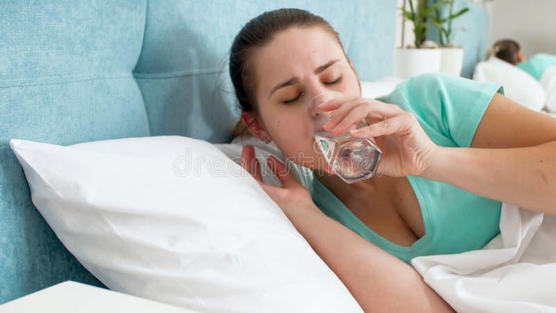 Porträt der jungen Frau liegend im Bett ein Trinkwasser vom Glas stockfotos