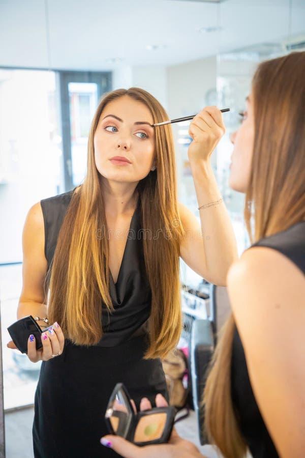 Porträt der jungen Frau Make-up nahe Spiegel machend stockbild