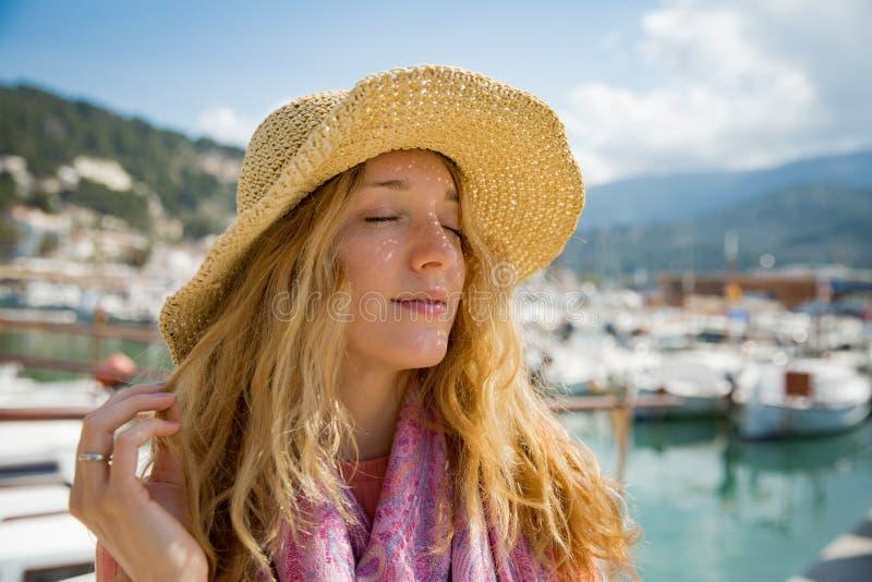 Porträt der jungen Frau mit dem hellen gelockten Haar im Strohhut lizenzfreie stockfotos