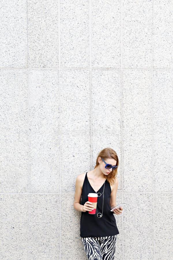 Porträt der jungen Frau mit Kaffee und Handy stockfotografie