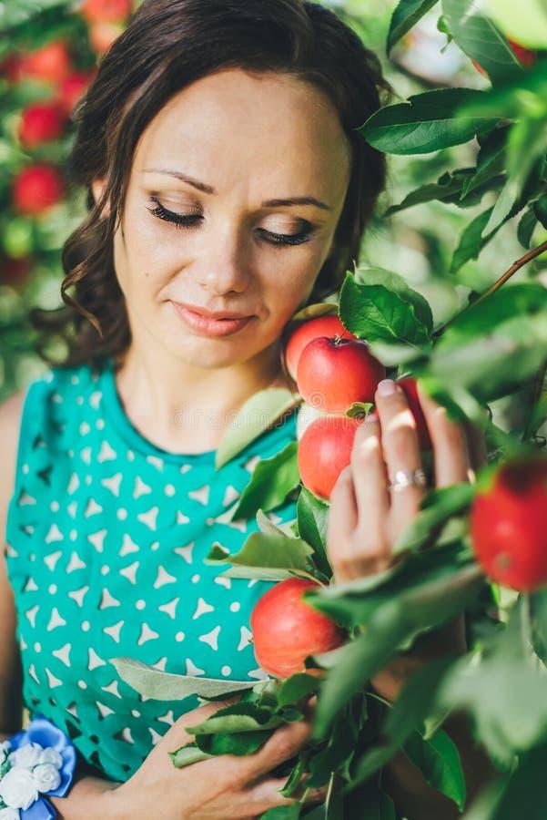 Porträt der jungen Frau mit rotem Apfel im Garten stockbild
