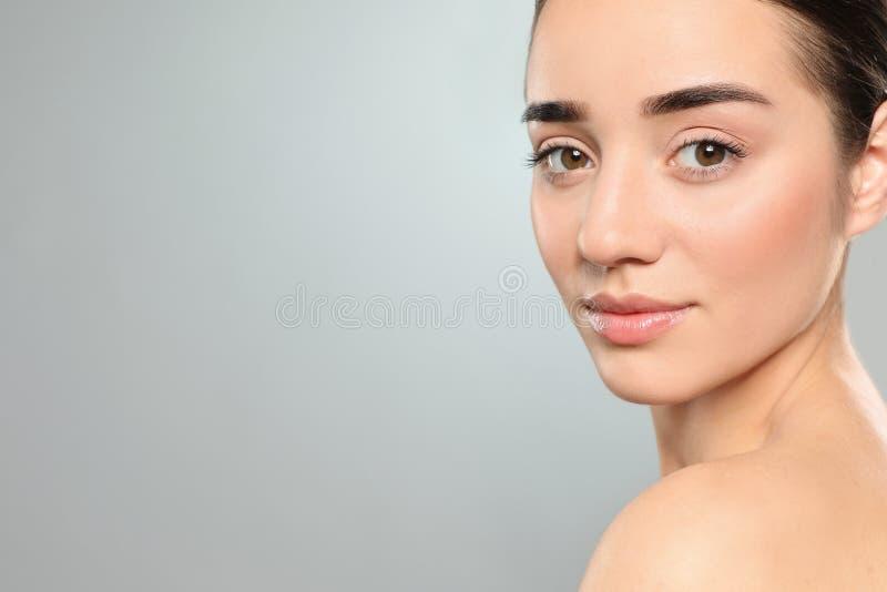 Porträt der jungen Frau mit schönem Gesicht gegen Farbhintergrund stockbild