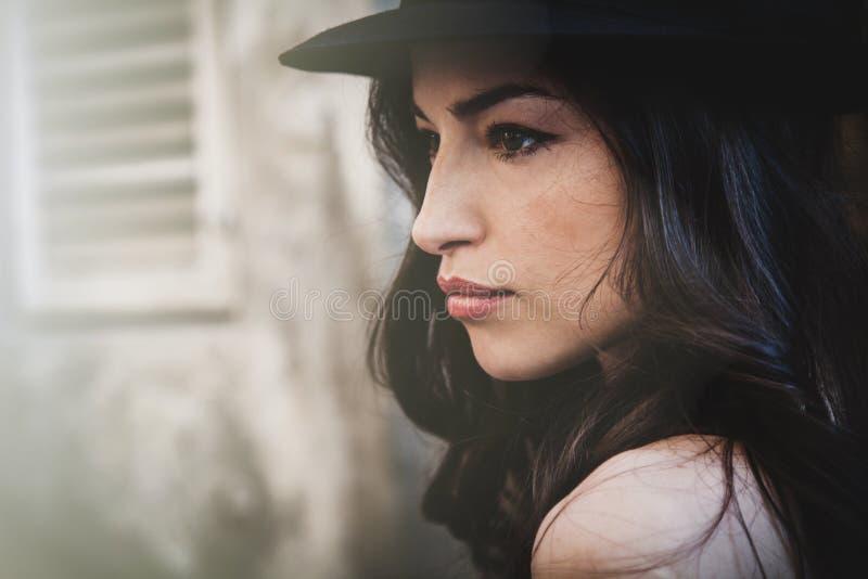 Porträt der jungen Frau mit Sommertagesprofil des Hutes im Freien lizenzfreies stockfoto
