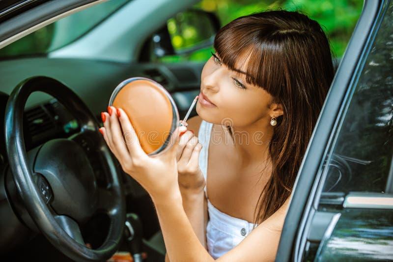 Porträt der jungen Frau oben im Auto machend lizenzfreie stockbilder