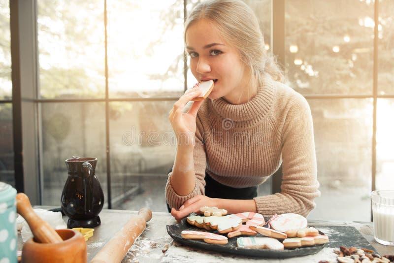 Porträt der jungen Frau Plätzchenherz essend lizenzfreies stockbild