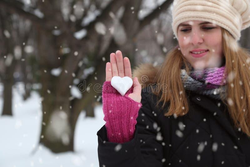 Porträt der jungen Frau Schneeherz in einem schneebedeckten Park zeigend Liebe lizenzfreies stockfoto