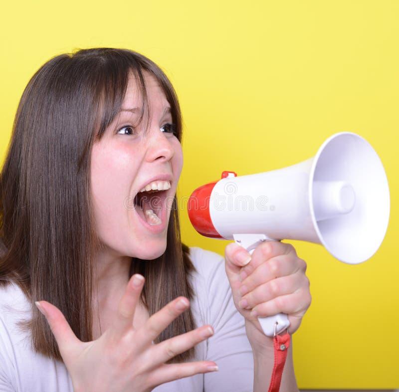 Porträt der jungen Frau schreiend mit einem Megaphon gegen Gelb stockfoto