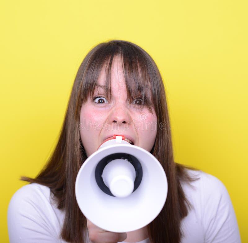 Porträt der jungen Frau schreiend mit einem Megaphon gegen Gelb stockbild