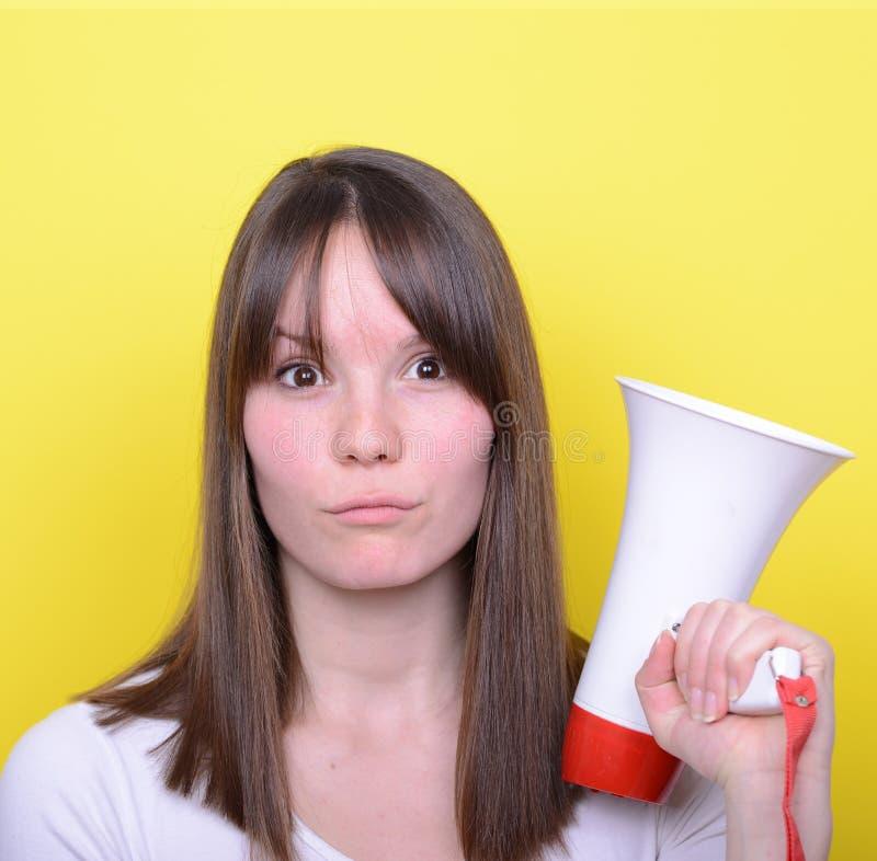 Porträt der jungen Frau schreiend mit einem Megaphon gegen Gelb stockfotografie