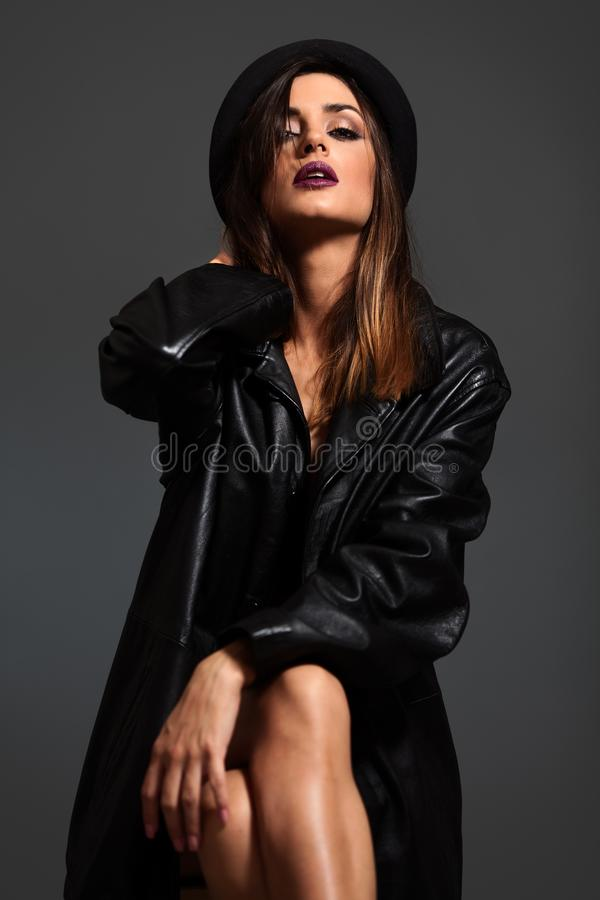 Porträt der jungen Frau in der schwarzen Lederjacke und im Hut stockbilder