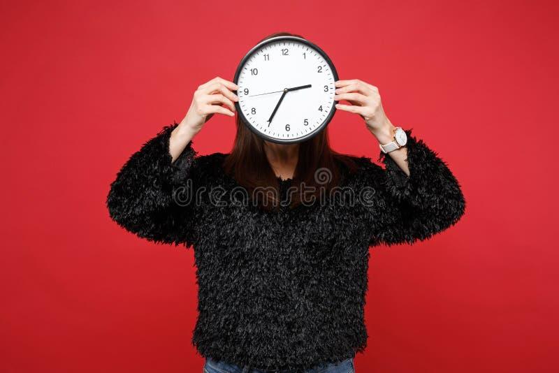 Porträt der jungen Frau in der schwarzen Pelzstrickjacke, die, Gesicht mit der runden Uhr bedeckend lokalisiert auf heller roter  lizenzfreies stockbild