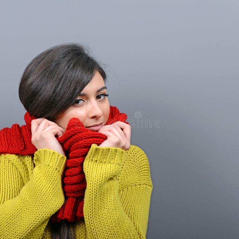 Porträt der jungen Frau in der Winterkleidung gegen grauen Hintergrund stockfoto